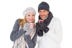 Ευτυχές ζεύγος στις κούπες εκμετάλλευσης χειμερινής μόδας Στοκ Φωτογραφία