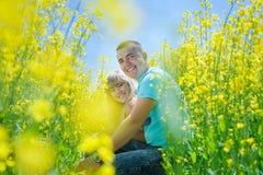 Ευτυχές ζεύγος στον κίτρινο τομέα βιασμών Στοκ φωτογραφία με δικαίωμα ελεύθερης χρήσης