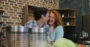Ευτυχές ζεύγος στο αγκάλιασμα ανδρών και γυναικών κουζινών που εξετάζει μεταξύ τους που προετοιμάζει τα τρόφιμα μαζί στο σπίτι απόθεμα βίντεο