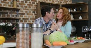 Ευτυχές ζεύγος στο αγκάλιασμα ανδρών και γυναικών κουζινών που εξετάζει μεταξύ τους στο σπίτι απόθεμα βίντεο