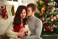 Ευτυχές ζεύγος στο εσωτερικό στο υπόβαθρο των διακοσμήσεων Χριστουγέννων Στοκ εικόνα με δικαίωμα ελεύθερης χρήσης