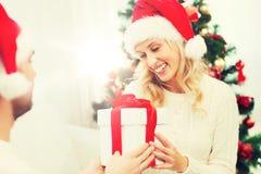 Ευτυχές ζεύγος στο σπίτι με το κιβώτιο δώρων Χριστουγέννων Στοκ Φωτογραφία