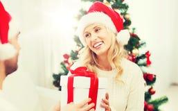 Ευτυχές ζεύγος στο σπίτι με το κιβώτιο δώρων Χριστουγέννων Στοκ Φωτογραφίες