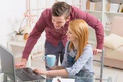 Ευτυχές ζεύγος στο σπίτι με το φορητό προσωπικό υπολογιστή στοκ φωτογραφία με δικαίωμα ελεύθερης χρήσης