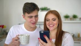 Ευτυχές ζεύγος στο σπίτι στην κουζίνα στο πρόγευμα που χρησιμοποιεί το smartphone που κοιτάζει βιαστικά μαζί on-line να έχε τον κ απόθεμα βίντεο