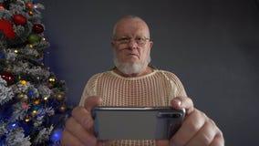 Ευτυχές ηλικιωμένο άτομο που κτενίζει την γκρίζα γενειάδα του με τη χτένα στο υπόβαθρο του χριστουγεννιάτικου δέντρου στις γιρλάν απόθεμα βίντεο