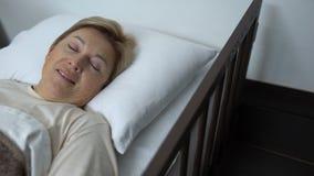 Ευτυχές ηλικιωμένο θηλυκό που βρίσκεται στο νοσοκομειακό κρεβάτι μετά από τη λειτουργία χειρουργικών επεμβάσεων, rehab απόθεμα βίντεο