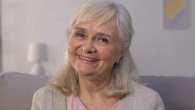 Ευτυχές ηλικιωμένο θηλυκό που χαμογελά και που εξετάζει τη κάμερα, ασφάλεια υγείας, προστασία φιλμ μικρού μήκους