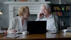 Ευτυχές ηλικιωμένο ανώτερο ζεύγος που χρησιμοποιεί το φορητό προσωπικό υπολογιστή και το smartphone απόθεμα βίντεο
