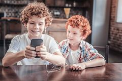 Ευτυχές θετικό αγόρι που εξετάζει την οθόνη smartphone Στοκ Φωτογραφία