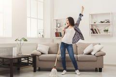Ευτυχές καθαρίζοντας σπίτι γυναικών με τη σφουγγαρίστρα και την κατοχή της διασκέδασης στοκ εικόνα με δικαίωμα ελεύθερης χρήσης