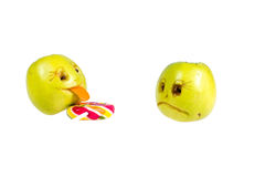 Ευτυχές και λυπημένο μήλο emoticons που γλείφει ένα lollipop υλοτομίες Στοκ φωτογραφία με δικαίωμα ελεύθερης χρήσης