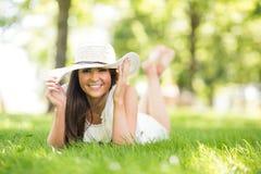 Ευτυχές καπέλο ήλιων εκμετάλλευσης γυναικών στο λιβάδι στοκ εικόνα με δικαίωμα ελεύθερης χρήσης