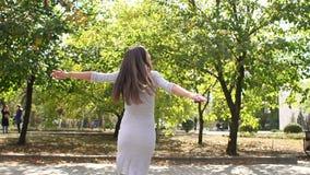 Ευτυχές καυκάσιο έγκυο κορίτσι που κτυπά την κοιλιά της που στέκεται κοντά στο μεγάλο δέντρο στο πάρκο φιλμ μικρού μήκους