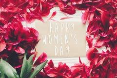 Ευτυχές κείμενο ημέρας γυναικών ` s στην κάρτα και κόκκινα πέταλα peonies σε αγροτικό Στοκ Εικόνες