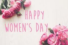 Ευτυχές κείμενο ημέρας γυναικών ` s στη ρόδινη ανθοδέσμη peonies στο αγροτικό άσπρο W στοκ φωτογραφία