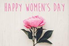 Ευτυχές κείμενο ημέρας γυναικών ` s στη ρόδινη ανθοδέσμη peonies στο αγροτικό άσπρο W Στοκ Εικόνα