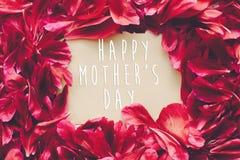 Ευτυχές κείμενο ημέρας μητέρων ` s στα κόκκινα πέταλα peonies στο αγροτικό άσπρο wo Στοκ φωτογραφία με δικαίωμα ελεύθερης χρήσης