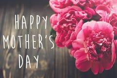 Ευτυχές κείμενο ημέρας μητέρων ` s στη ρόδινη ανθοδέσμη peonies στο αγροτικό σκοτεινό W Στοκ Φωτογραφίες