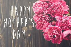 Ευτυχές κείμενο ημέρας μητέρων ` s στη ρόδινη ανθοδέσμη peonies στο αγροτικό σκοτεινό W Στοκ Φωτογραφία