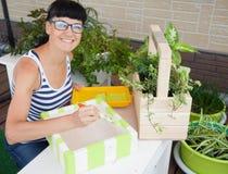 Ευτυχές κιβώτιο ζωγραφικής γυναικών χαμόγελου για τα λουλούδια πράσινα δοχεία λουλου&del Στοκ Φωτογραφίες