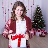 Ευτυχές κιβώτιο χριστουγεννιάτικου δώρου ανοίγματος γυναικών στο διακοσμημένο δωμάτιο Στοκ εικόνες με δικαίωμα ελεύθερης χρήσης