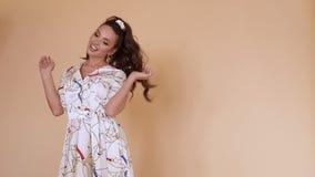 Ευτυχές κομψό κορίτσι στο άσπρο παιχνίδι φορεμάτων με μακρυμάλλη απόθεμα βίντεο