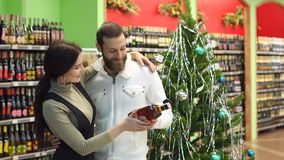 Ευτυχές κονιάκ αγοράς ζευγών σε ένα κατάστημα που στέκεται κοντά σε ένα διακοσμημένο χριστουγεννιάτικο δέντρο φιλμ μικρού μήκους