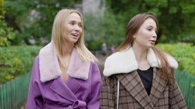 Ευτυχές κορίτσι δύο που παίρνει έναν περίπατο την υγρή ημέρα πτώσης που φορά τα μοντέρνα παλτά, νέα κορίτσια στη μοντέρνη εξάρτησ απόθεμα βίντεο