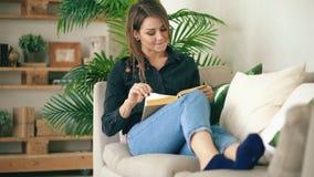 Ευτυχές κορίτσι εφήβων που στηρίζεται στον καναπέ στο καθιστικό διαβάζοντας το αγαπημένο νέο βιβλίο της στο σπίτι απόθεμα βίντεο