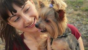 Ευτυχές κορίτσι και λατρευτή τοποθέτηση τεριέ του Γιορκσάιρ σκυλιών υπαίθρια στο ηλιοβασίλεμα στο πάρκο φθινοπώρου απόθεμα βίντεο