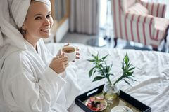 Ευτυχές κορίτσι με ένα φλιτζάνι του καφέ Γυναίκα χαλάρωσης εγχώριου ύφους που φορά το μπουρνούζι και την πετσέτα μετά από το ντου στοκ φωτογραφίες με δικαίωμα ελεύθερης χρήσης