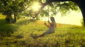Ευτυχές κορίτσι με μακρυμάλλη, ταλαντεμένος στην ταλάντευση στον κλάδο δέντρων, στις φωτεινές ακτίνες ενός χρυσών ηλιοβασιλέματος απόθεμα βίντεο
