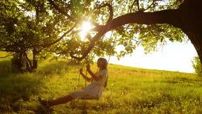 Ευτυχές κορίτσι με μακρυμάλλη, ταλαντεμένος στην ταλάντευση στον κλάδο δέντρων, στις φωτεινές ακτίνες ενός χρυσών ηλιοβασιλέματος φιλμ μικρού μήκους