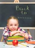 Ευτυχές κορίτσι με τα βιβλία και το μήλο. Στοκ Εικόνες