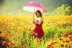 ευτυχές κορίτσι με τη ρόδινη ομπρέλα πέρα από τον κόκκινο τομέα παπαρουνών στοκ εικόνες