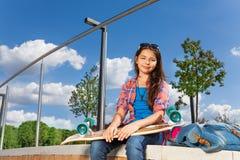 Ευτυχές κορίτσι με skateboard το μόνο εξωτερικό καθίσματος Στοκ εικόνα με δικαίωμα ελεύθερης χρήσης