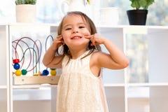 Ευτυχές κορίτσι μικρών παιδιών που κάνει ένα αστείο πρόσωπο στοκ φωτογραφίες