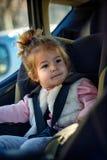 Ευτυχές κορίτσι μικρών παιδιών που κουμπώνεται στο κάθισμα αυτοκινήτων της Στοκ φωτογραφία με δικαίωμα ελεύθερης χρήσης