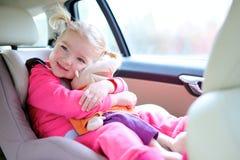 Ευτυχές κορίτσι μικρών παιδιών που απολαμβάνει το ασφαλές ταξίδι στο αυτοκίνητο Στοκ Φωτογραφία