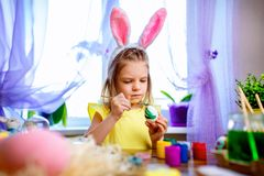 Ευτυχές κορίτσι Πάσχας στα αυτιά λαγουδάκι που χρωματίζει τα αυγά, μικρό παιδί στο σπίτι Διακοπές άνοιξη στοκ εικόνες με δικαίωμα ελεύθερης χρήσης