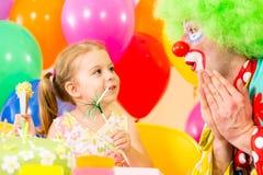 Ευτυχές κορίτσι παιδιών με τον κλόουν στη γιορτή γενεθλίων στοκ εικόνα