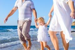 Ευτυχές κορίτσι παιδιών με τους γονείς που κρατούν τα χέρια και που έχουν τη διασκέδαση που περπατά στην παραλία Οικογενειακές δι Στοκ Εικόνες