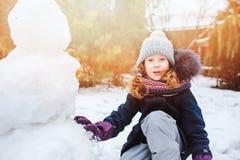 ευτυχές κορίτσι παιδιών που κάνει το άτομο χιονιού στις διακοπές Χριστουγέννων στο κατώφλι Στοκ φωτογραφία με δικαίωμα ελεύθερης χρήσης
