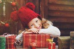 Ευτυχές κορίτσι παιδιών στα κόκκινα δώρα Χριστουγέννων καπέλων και μαντίλι τυλίγοντας στο άνετο εξοχικό σπίτι, που διακοσμείται γ Στοκ εικόνα με δικαίωμα ελεύθερης χρήσης