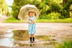 Ευτυχές κορίτσι παιδιών στο φόρεμα με μια ομπρέλα και λαστιχένιες μπότες στη λακκούβα στοκ εικόνα με δικαίωμα ελεύθερης χρήσης
