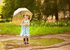 Ευτυχές κορίτσι παιδιών στο φόρεμα με μια ομπρέλα και λαστιχένιες μπότες στη λακκούβα στον περίπατο στοκ φωτογραφία