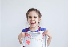 Ευτυχές κορίτσι, παιδί με την άσπρη διακοσμημένη σχέδιο μπλούζα Στοκ Φωτογραφίες
