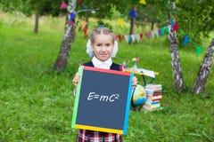 Ευτυχές κορίτσι παιδιών παιδιών μαθητριών που κρατά έναν πίνακα κιμωλίας με μια μορφή Στοκ Φωτογραφία