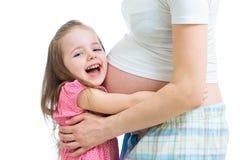 Ευτυχές κορίτσι παιδιών που αγκαλιάζει την κοιλιά της έγκυου μητέρας Στοκ φωτογραφία με δικαίωμα ελεύθερης χρήσης